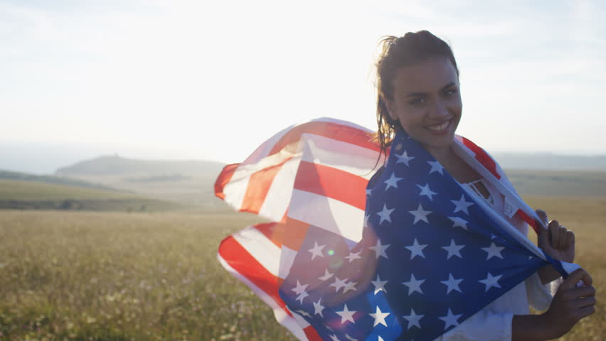 4K Beautiful woman wearing a US flag in the countryside, in slow motion