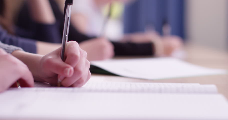 4k, Students in school uniform taking exam at desk in a classroom. Slow motion.
