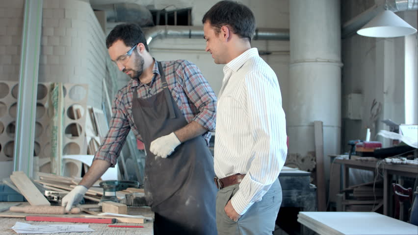 The boss pays the carpenter in workshop. | Shutterstock HD Video #18871019