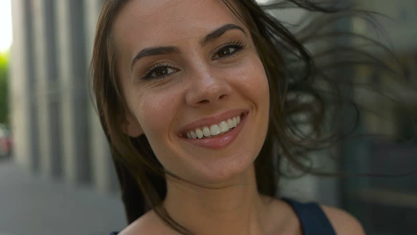 Wonderful smiling woman with a lovely look and natural make up looking at camera and the wind moving her hair | Shutterstock HD Video #18899135