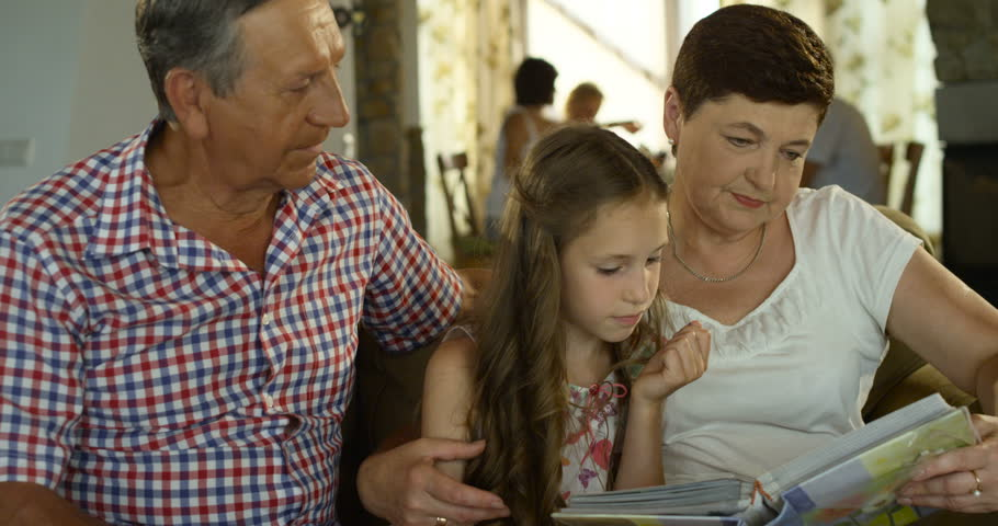 Smiling grandfather, granddaughter and grandmother with book or photo album sitting on couch at home | Shutterstock HD Video #18899309