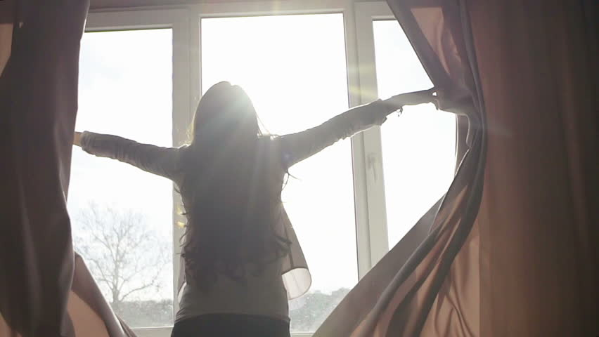 Attractive young woman opens curtains in slow motion is looking at the sunrise standing near the window in her home and enjoys of city view from height self isolation, infection, coronavirus, home