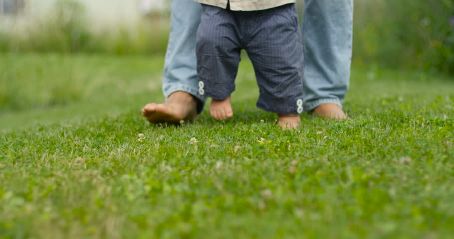Father learns child walk outdoors. Baby first steps on grass, slow motion.