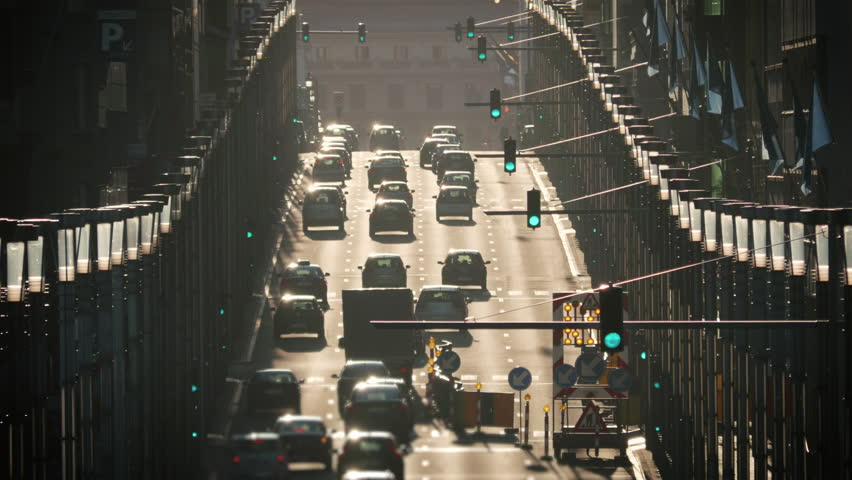 Busy street traffic Brussels cars commute sunny day golden hour green lights commercial use #18937559