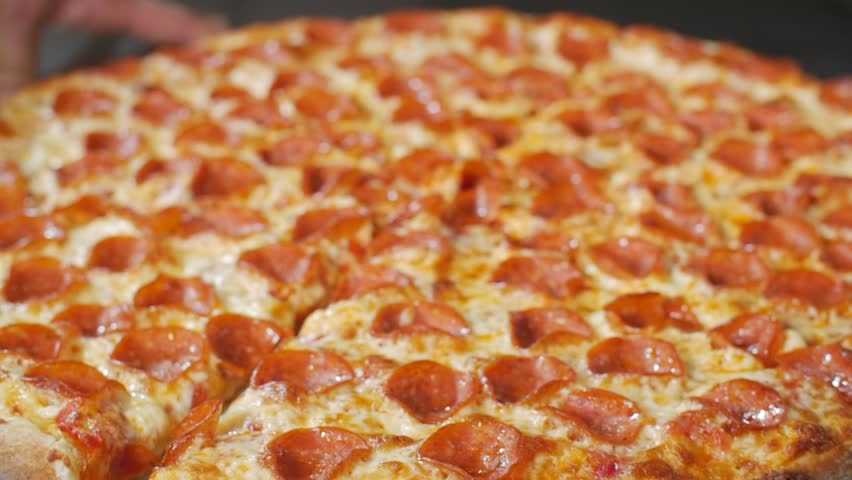 Slow motion close-up of steaming pepperoni pizza cooked in restaurant in a commercial industrial stone oven #18943523