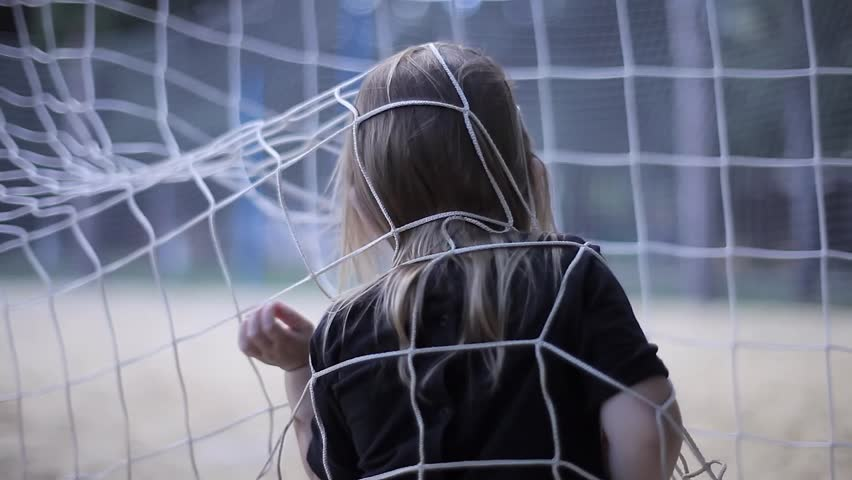 Shaggy Baby Blonde Girl in a Dark Suit Playing Near Soccer Net