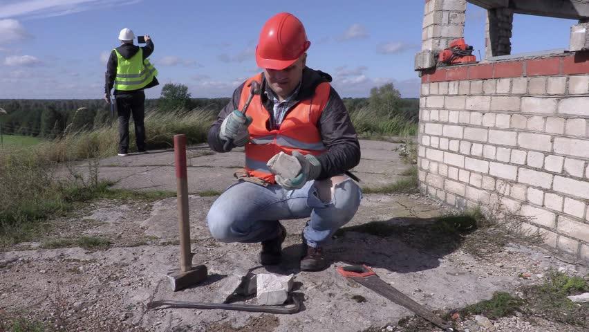 Construction worker divides brick with hammer   Shutterstock HD Video #18953627