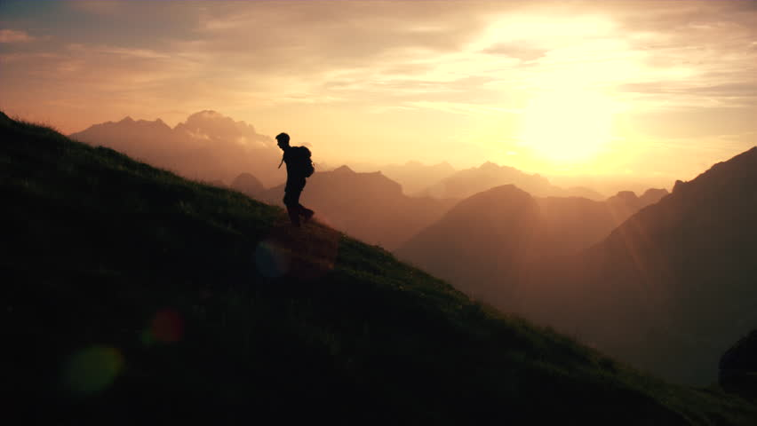 Aerial - Epic shot of a man hiking on the edge of the mountain as a silhouette in beautiful sunset (edited version) | Shutterstock HD Video #18955577