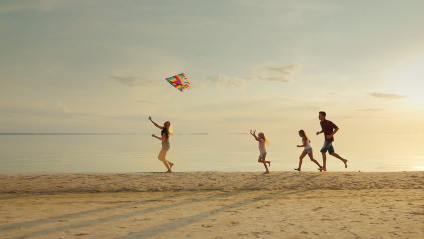 Happy and carefree childhood. Children playing with older kite, running across the sand, laughing | Shutterstock HD Video #18957323