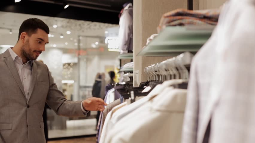 Sale, shopping, fashion, style and people concept - elegant young man in suit choosing clothes in mall or clothing store | Shutterstock HD Video #18964663