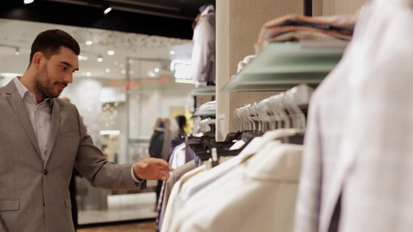 Sale, shopping, fashion, style and people concept - elegant young man in suit choosing clothes in mall or clothing store | Shutterstock HD Video #18964690