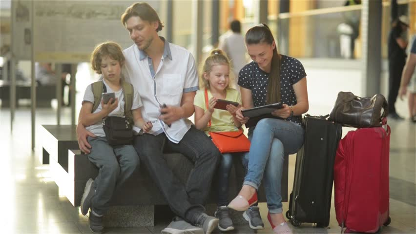 Family waiting for your flight or train and use the tablet and phones while sitting in waiting room of airport or railway station.
