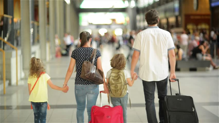 Happy family with little girl and boy going on railway station, mother father and the kids walk through the airport with suitcases
