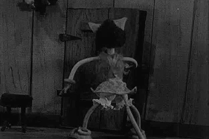 In a stop-motion animation, a male dog kisses his girlfriend, a female cat, before a villain pulls her through a window and runs off with her in the 1940s. (1940s)