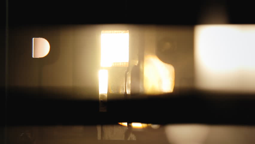 Inside a super 8mm film projector: the shutter; visible as a black, out-of-sync silhouette in front of the lamp's intense light. Macro detail shot.