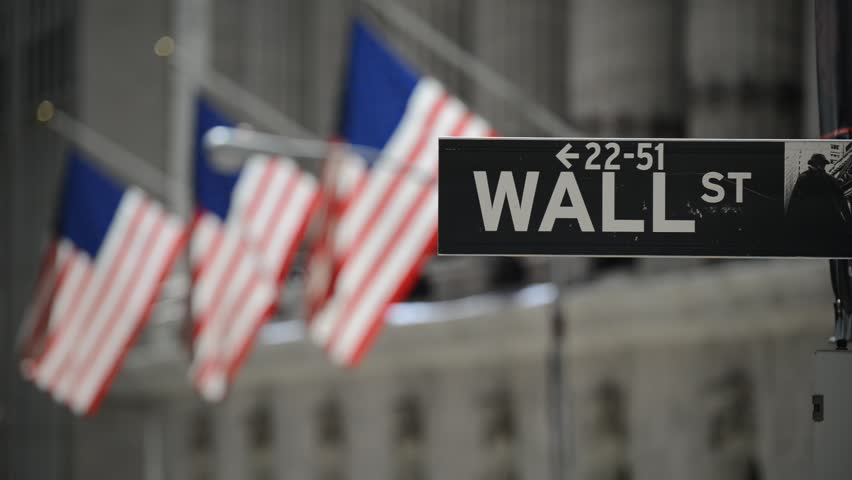 Wall Street sign with American flags purposely blurred in background, HD video