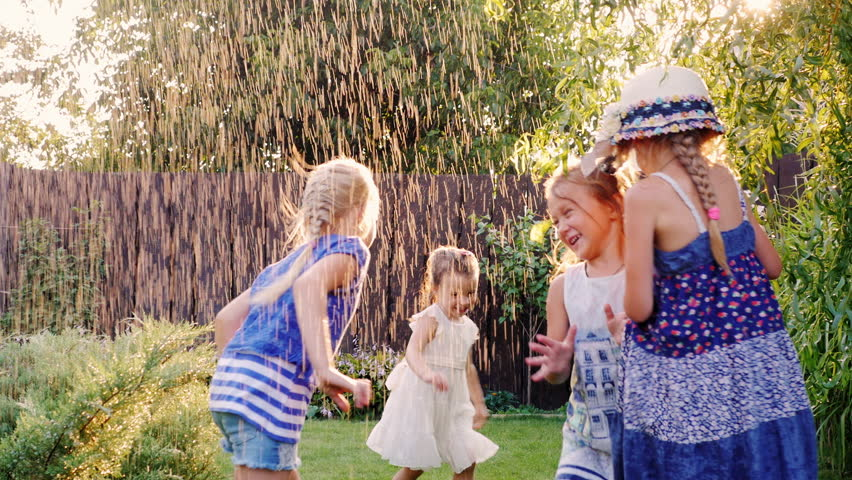 Carefree fun children play in the garden. Laughing, running under the jets of water or rain | Shutterstock HD Video #18983773