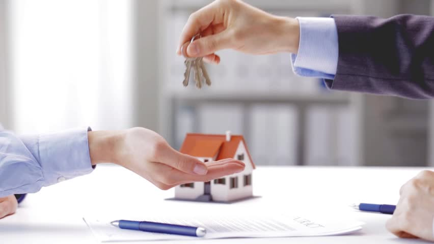 Business, real estate, deal and people concept - man giving house keys to woman at office at office