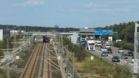 Frankfurt, Germany - August 08, 2016: ICE highspeed train railroad next to heavily frequented German highway A3 between Frankfurt Airport and Raunheim. Pannning shot.