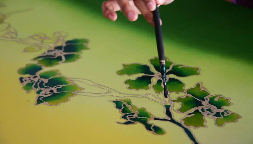 Close-up of an artist carefully touch-up the floral/flower motif on a yellow traditional batik fabric