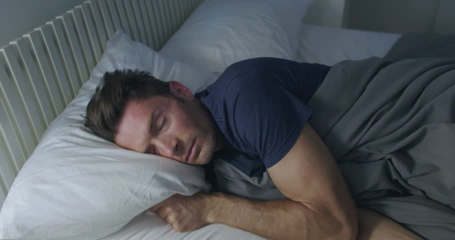 Sleeping man turns towards light while dreaming in a double bed with soft ambient light.  Camera move on jib arm.  Side view, medium shot. | Shutterstock HD Video #18996688