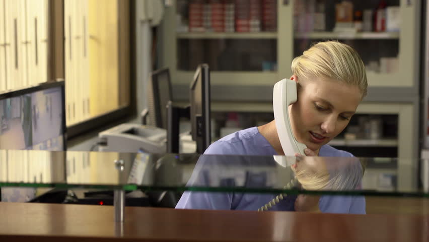 Young woman at work as receptionist and nurse in hospital and talking on the phone