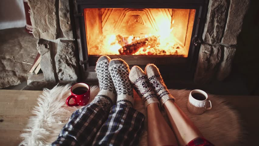 Couple Feet in Woollen Socks by the Cozy Fireplace, 4K. Man and Woman relax by warm fire and warming up their feet. Close up. Winter and Christmas holidays concept.  #19022782