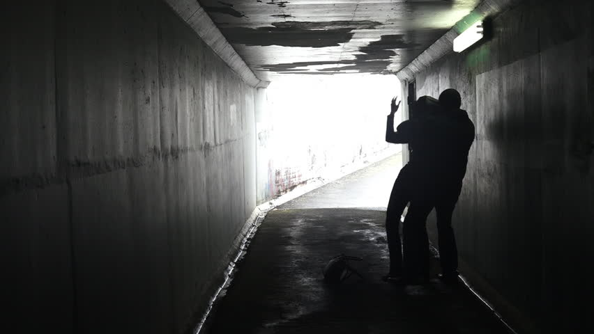 Silhouette of a criminal adult male attacks a young adult woman from behind in an underground dark alleyway tunnel. Violence against women concept with copy space.