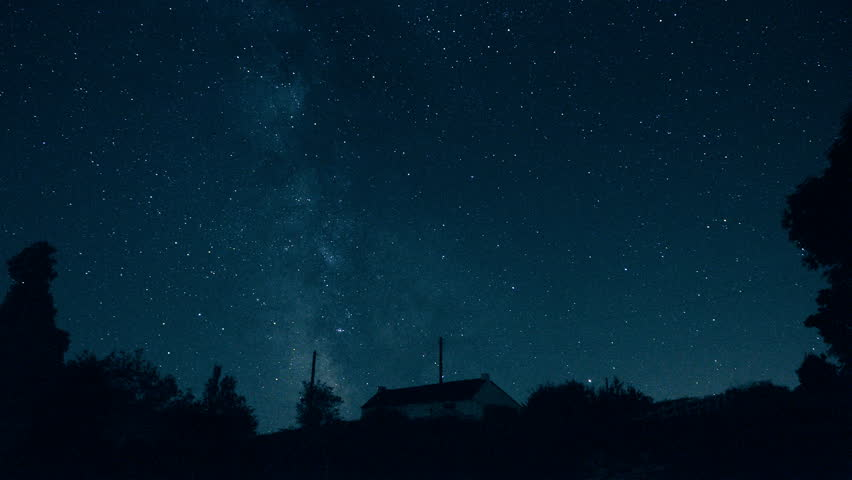 """Stars and the Milky Way moving in the sky - Starry night sky in timelapse - ISS flashes at 2""""17 (top center) - Looking to southwest from western Europe above an isolated house in countryside."""