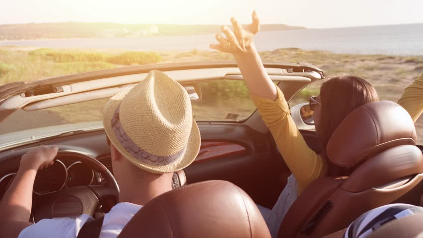 Cute Young Couple Driving At Sea Front Woman Enjoying Waiving Arms In The Air In Convertible Car Wind Blowing Hair Summer Fun Vacation Adventure Concept #19037440