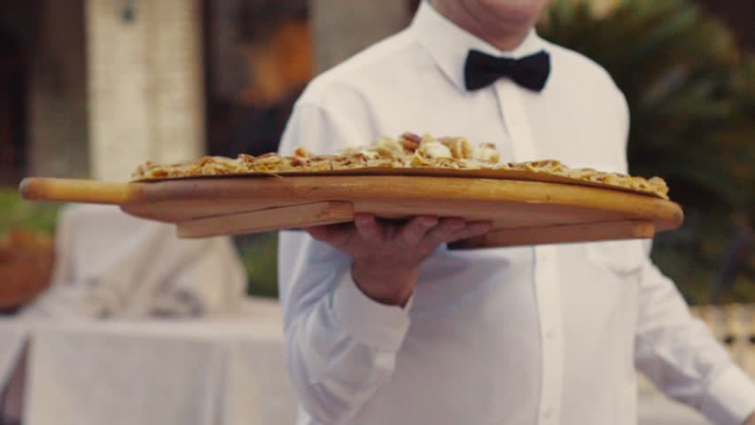 A young waiter in the restaurant serving banquet, delivers delicious Italian dishes on a large wooden plate, in slow motion. Italian cuisine, restaurant staff. Outside shooting.