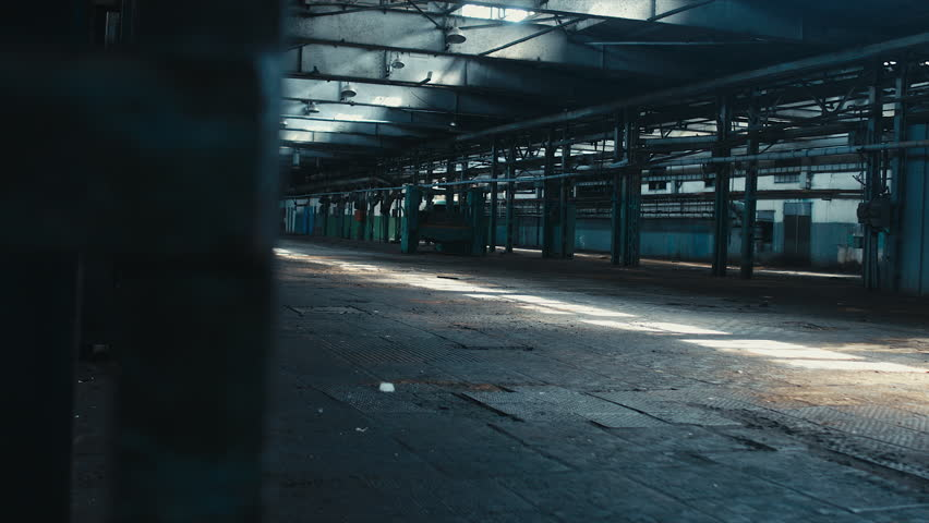 Left to right dolly wide angle shot of abandoned factory interior. Scary, catastrophe, horror concept. RAW graded footage