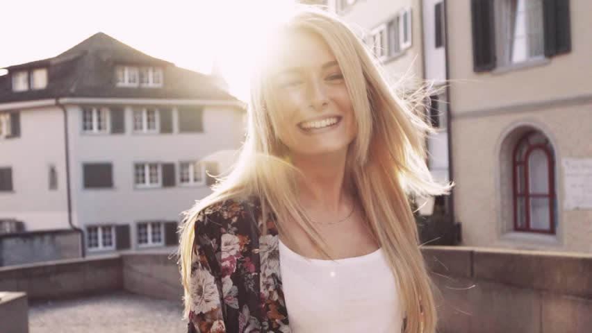 Young blonde girl is wondering down the Italian streets. Cute smile. Summer, sun is shining, Italian evening, sunset. No people around, female portrait. Slow motion, close up view, stabilizer shots.