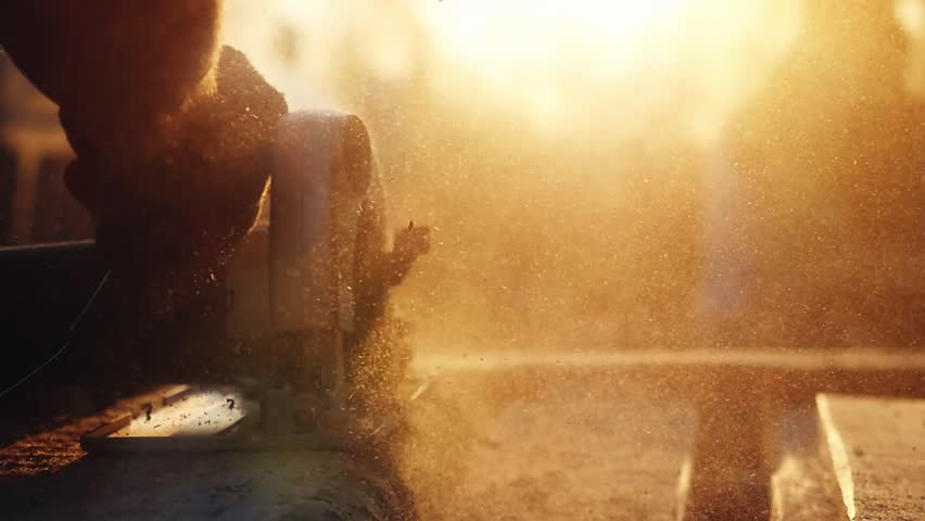 Man is craft working at a work bench with power tools in slowmotion during sunset with beautiful lens flare. 1920x1080