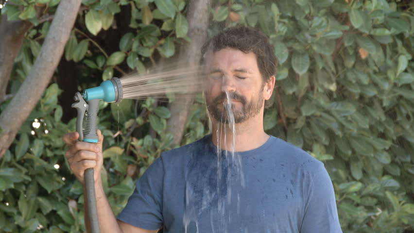 Slow motion of model released man spraying himself in the face with a hose outside on a hot summer's day.