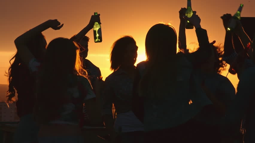 Silhouettes of young people toasting with beer bottles and dancing with raised arms to the music played by dj at rooftop party during beautiful city sunset