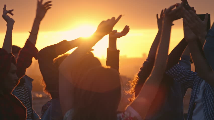Group of young multi-ethnic people having fun dancing with raised arms to the music played by dj at rooftop party at sunset #19079284