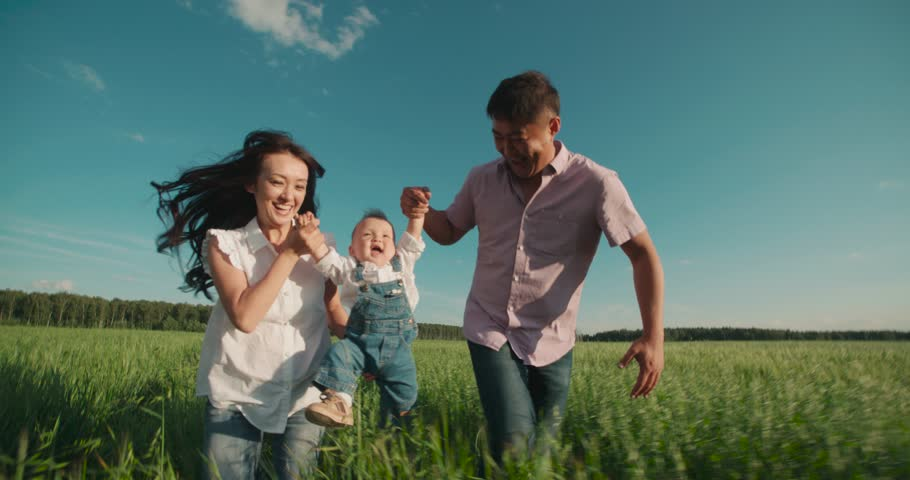 Happy Asian family with small child 1 year running on the green field, slow motion