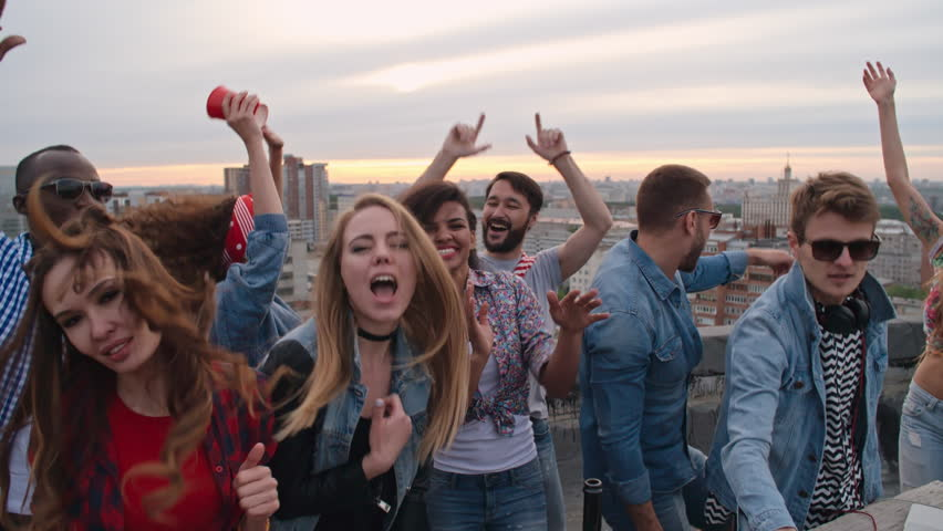 High angle view of crowd of happy multi-ethnic young people looking at camera while dancing to the music played by dj at rooftop party | Shutterstock HD Video #19098388