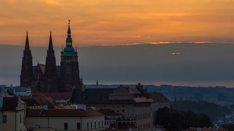 A beautiful view of Prague at sunrise on a misty morning timelapse. Prague Castle and St. Vitus Cathedral on the left and a golden rising sun in the background. Close up view