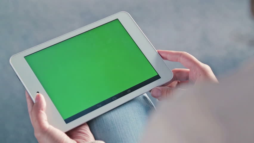 Woman looking at tablet with green screen. Close up shot of woman's hands with pad