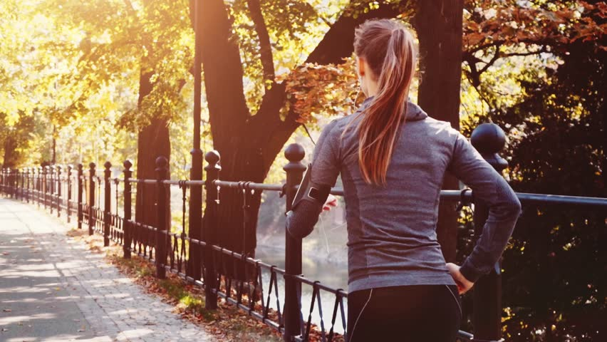 Runner Woman Running in the Sunny City Park Exercising Outdoors. Steadicam STABILIZED shot, SLOW MOTION 120 fps. Sportswoman Listening to Music during Morning Training. Healthy Lifestyle. Lens Flare. #19127008