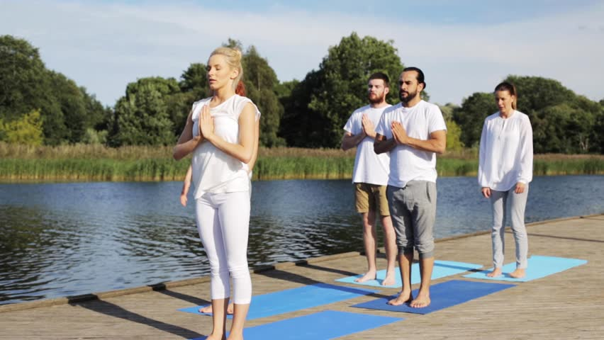 Fitness, sport, and healthy lifestyle concept - group of people making yoga exercises on river or lake berth   Shutterstock HD Video #19160911