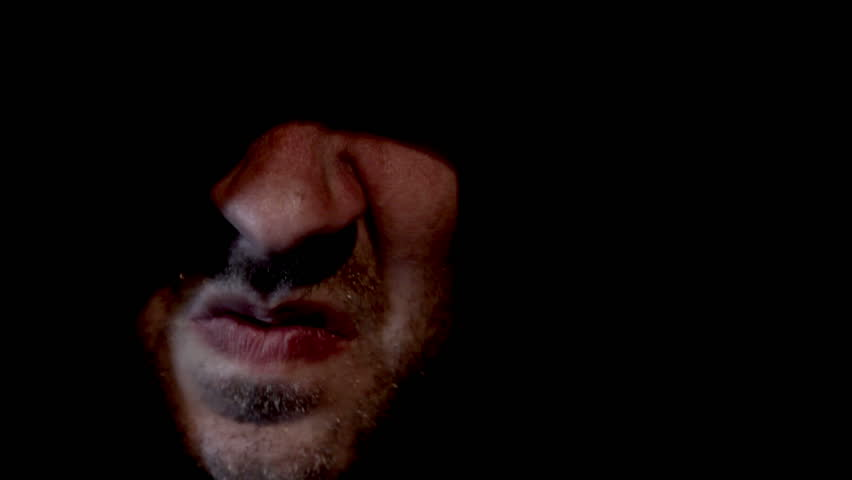 Scary hooded man appearing from darkness screaming