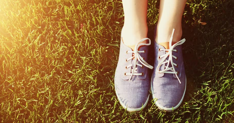 Female feet in sneakers gumshoes moving and posing on a sunlit green grass, close up. Woman's feet in blue jeans color sports shoes. Slow motion, 120fps. 4K, DCi. Lens flare. #19183780