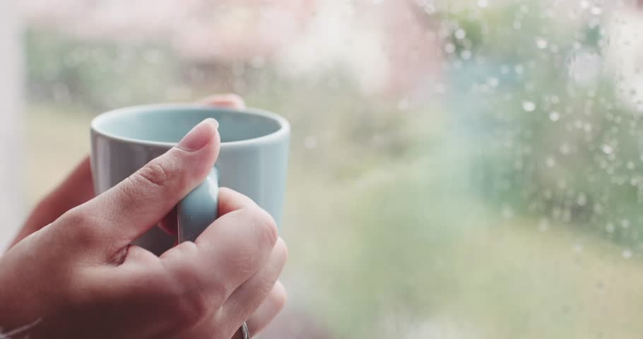 Young Woman Enjoying her morning coffee or tea, Looking Out the Rainy Window. 4K DCi SLOW MOTION 120 FPS. Beautiful romantic unrecognizable girl drinking hot beverage at cozy home. Rainy Day Mood.