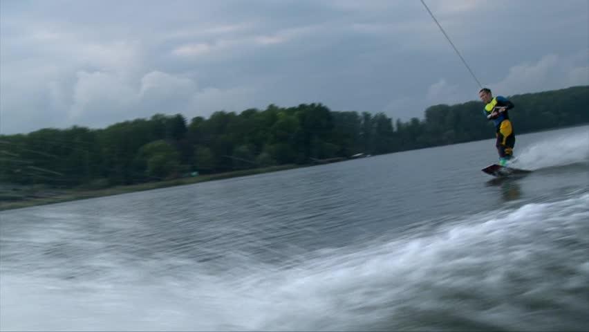 Asian man wakeboarding  behind a boat, water splashing, wake-board in cold water