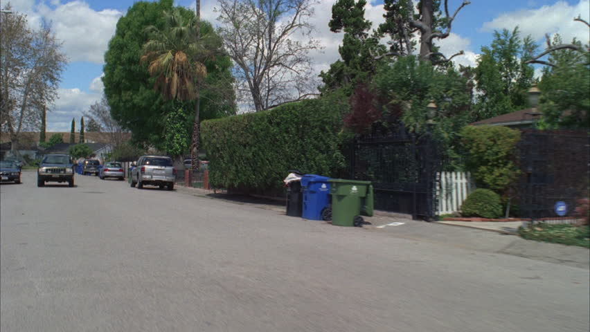 Day Process Plate 45 driver Residential neighborhood, middle class no sidewalks Black SUV following Green bare trees palms Fluffy clouds   Shutterstock HD Video #19233400