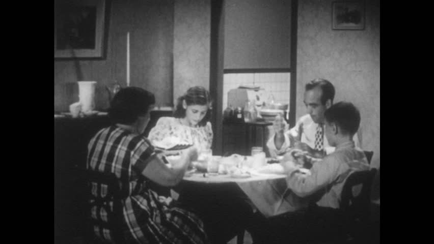 UNITED STATES 1950s: Family eating at table, zoom in on food / Close up, man eating.