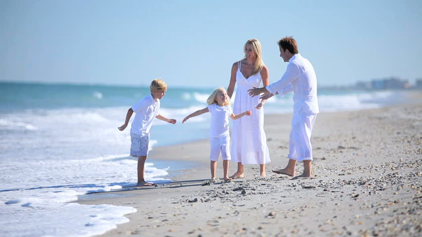 Attractive young parents having fun with their children on the beach